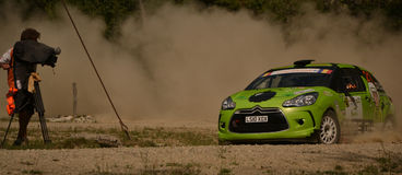 Drifting rally car and a camera operator (wide) Royalty Free Stock Image