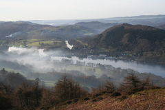 Drifting Smoke. Smoke from a fire drifts over the southern end of Windermere in Englands lake District stock photography