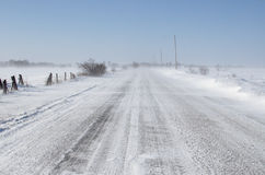 Drifting snow on rural road Royalty Free Stock Image
