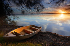 Drifting to new shores as the sun sets on another day. Sublime scene and tranquil waters reflecting like a mirror as the divine sun sets casting its golden Stock Image