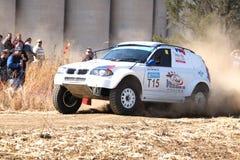 Drifting white BMW rally car kicking up dust on turn. Royalty Free Stock Photo