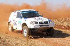 Drifting white BMW rally car kicking up dust on turn. Stock Images