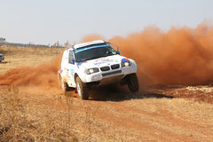 Drifting white BMW rally car kicking up dust on turn. Stock Photo