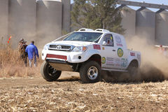 Drifting white Toyota truck kicking up dust on turn ar rally. Royalty Free Stock Photography