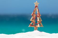 Driftwood Christmas tree decorated with string of red baubles at stock photo