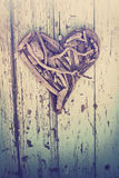 Driftwood heart on vintage wall Stock Images