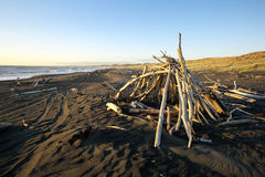 Driftwood hut on black sand beach Royalty Free Stock Image