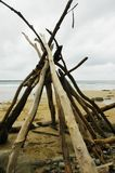 Driftwood stacked into a teepee on a deserted beach. Long branches of driftwood have been stacked into a teepee-shape on a beach. Pebbles and stones are at the Stock Photos
