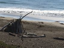 Driftwood Tepee. A white-washed driftwood tepee on Moonstone beach offers shelter from the hot sun & wind on the beach Royalty Free Stock Photo