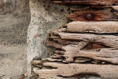 Driftwood z rdzewiejącymi ryglami ustawia przeciw betonowej kamiennej ścianie, rocznika grunge tło zdjęcia stock
