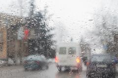 Drijf voorzichtig altijd auto wanneer het regent Regen op de stadsstraat door een autowindscherm Stock Afbeelding