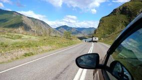 Drijfmening van kant van de berg schitterende vallei van de autospiegel Mooi landschap van een weg in de bergen op zonnig stock videobeelden