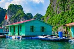 Drijvend dorp dichtbij rotseilanden in Halong-Baai stock fotografie