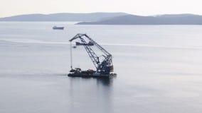 Drijvende kraan op de achtergrond van de eiland Russische zeilen door het Bosphorus-Oosten in de stad Van het Verre Oosten van Vl