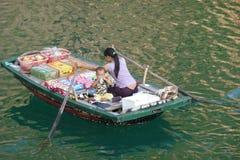 Drijvende voedselverkoper met baby in Baai Halong Stock Foto