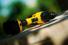 Drill. Hand cordless drill and electric screwdriver on wood planks Royalty Free Stock Photos