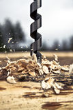 A drill bit in a motion. The drill bit making a hole in the log Royalty Free Stock Photo