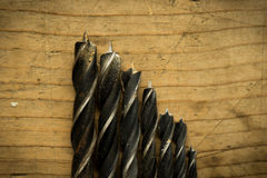 Drill bits close up on wooden table Royalty Free Stock Photos