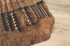 Drill bits in leather tool roll on a wooden workbench Stock Images