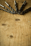Drill bits on wooden table Stock Image