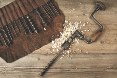 Drill brace with bits in leather tool roll on a wooden workbench Royalty Free Stock Photography