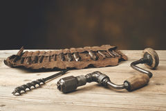 Drill brace with bits in leather tool roll on a wooden workbench Stock Photography