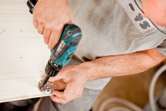 Drill driver in focus with carpenter Stock Photos
