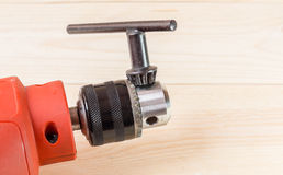 Drill. Electric drill head and drill key on wooden background Royalty Free Stock Images