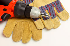 Drill and gloves Stock Images