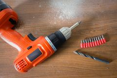 Drill machine and on wooden table with a lot of dust Royalty Free Stock Photography