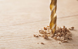 Drill makes a hole in the wooden oak table with wood. Drill makes hole in the wooden oak table wood Royalty Free Stock Image