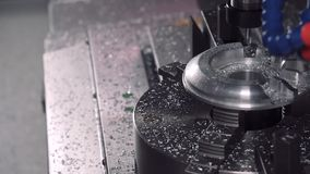 Drill milling shapes out of a metal piece on a CNC machine stock video footage