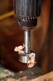 Drill press with a forstner bit attached. Bits of wood shavings are clinging on. Close up stock images