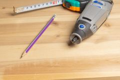 Drill rotary tool, tape measure and pencil on the furniture blank royalty free stock image