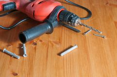 A drill on a wood table. Drill, screws and wall plugs on a wood table Stock Photography