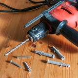 A drill on a wood table. Drill, screws and wall plugs on a wood table Stock Image