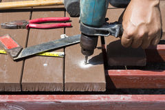 Drill setting screws in artificial wood for patio Stock Photos