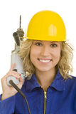 Drill on the shoulder. Young woman with helmet and jumpsuit carrying a drill machine on her shoulder Royalty Free Stock Photos