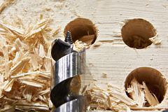 Drill for wood, hole of board and shavings Royalty Free Stock Image
