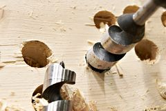 Drill for wood in hole of board and shavings Stock Image
