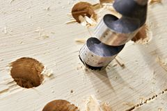 Drill for wood in hole of board and shavings Stock Photography