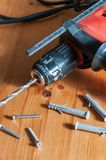 A drill on a wood table. Drill, screws and wall plugs on a wood table Royalty Free Stock Image
