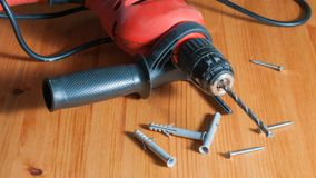 A drill on a wood table. Drill, screws and wall plugs on a wood table Stock Photos