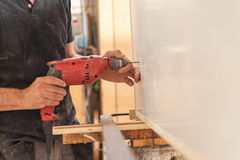 Drill in woodworker`s hands in action Royalty Free Stock Photos
