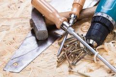 Drillborr med timmer, skruvmejslar och skruvar Arkivfoton