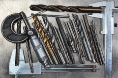 Drillborrbitar med mikrometer och klämmor på metallbakgrund Arkivbild