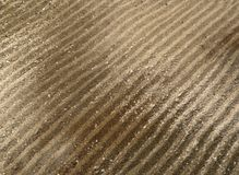 Drilled lines in brown sand surface Royalty Free Stock Photography