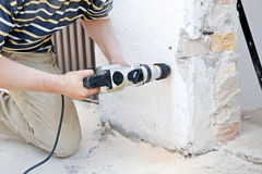 Drilling. A man drilling a hole in a white wall Royalty Free Stock Images