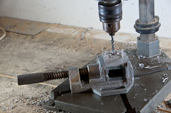 Drilling into a block of metal. With a lot of cuttings Stock Photos