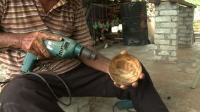 Drilling Into Coconut Shell. Handheld, medium close up shot of a man drilling into a coconut shell stock video footage
